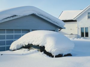 car outside of garage covered in deep snow there are many benefits to parking your car inside